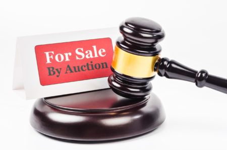 Gavel on a white background in front of a property auction sign